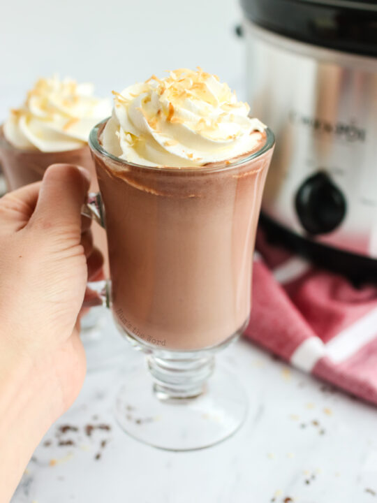 hand holding up a cup of hot chocolate with a second cup in the background with crockpot