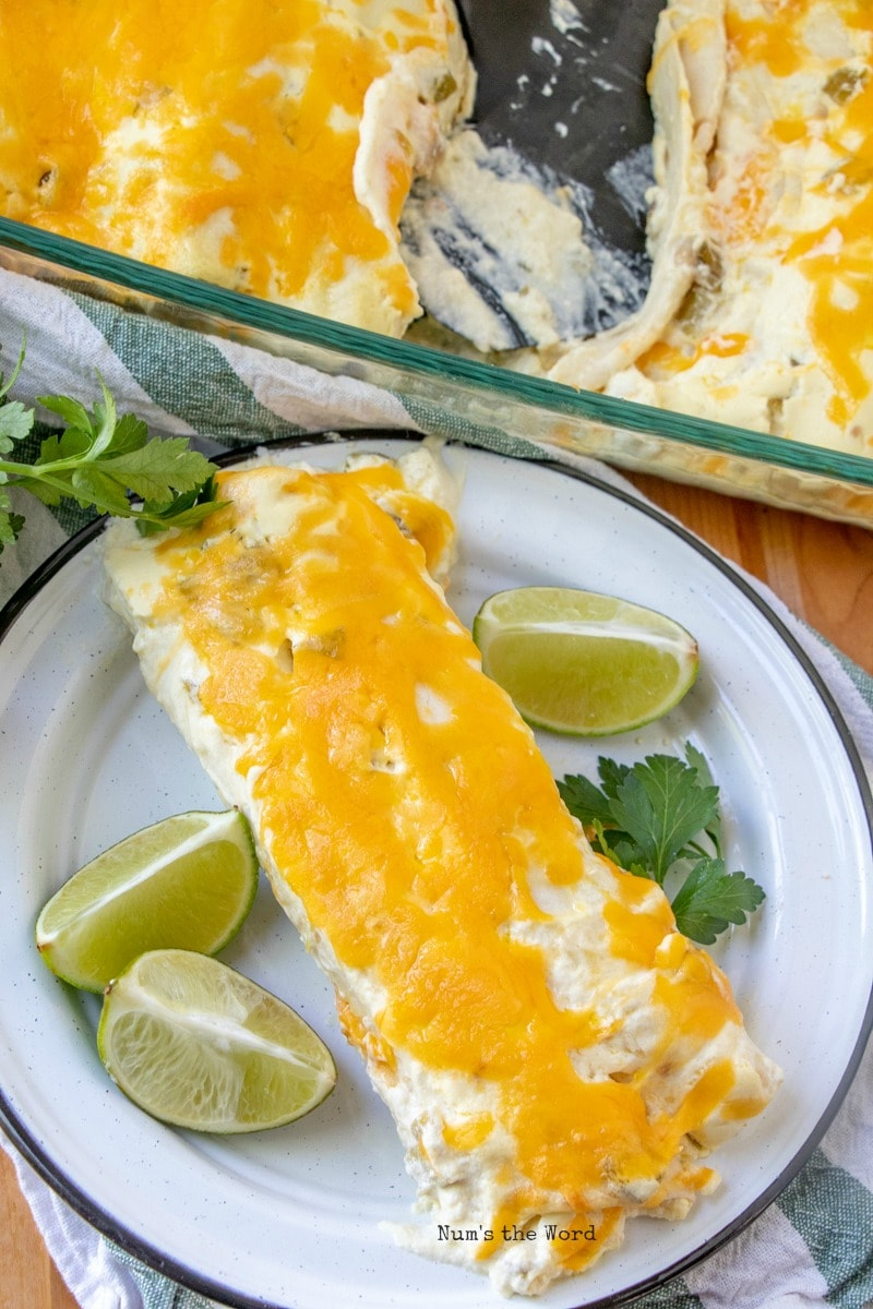 Cheesy Chicken Enchiladas - enchiladas on plate with lime wedges and cilantro