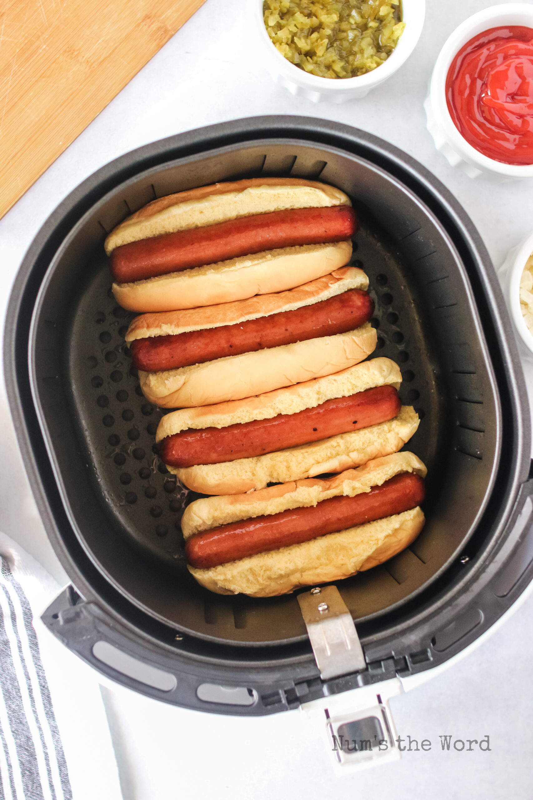 cooked hot dogs with buns in the air fryer, ready to serve.