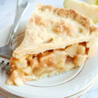 slice of pear pie on a plate, showing juice pears in cinnamon sauce ready to be eaten - zoomed in image.