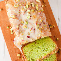 A loaf of bread on a cutting board with almond icing and chopped nuts drizzled on top. Two slices have been cut off.