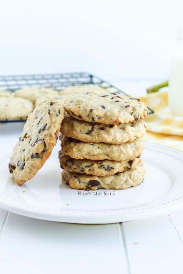 Banana Oatmeal Chocolate Chip Cookies - cookies stacked on a plate with one cookie on side.