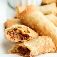 egg rolls on a plate with bowl of salsa in background. One egg roll cut in half to show filling