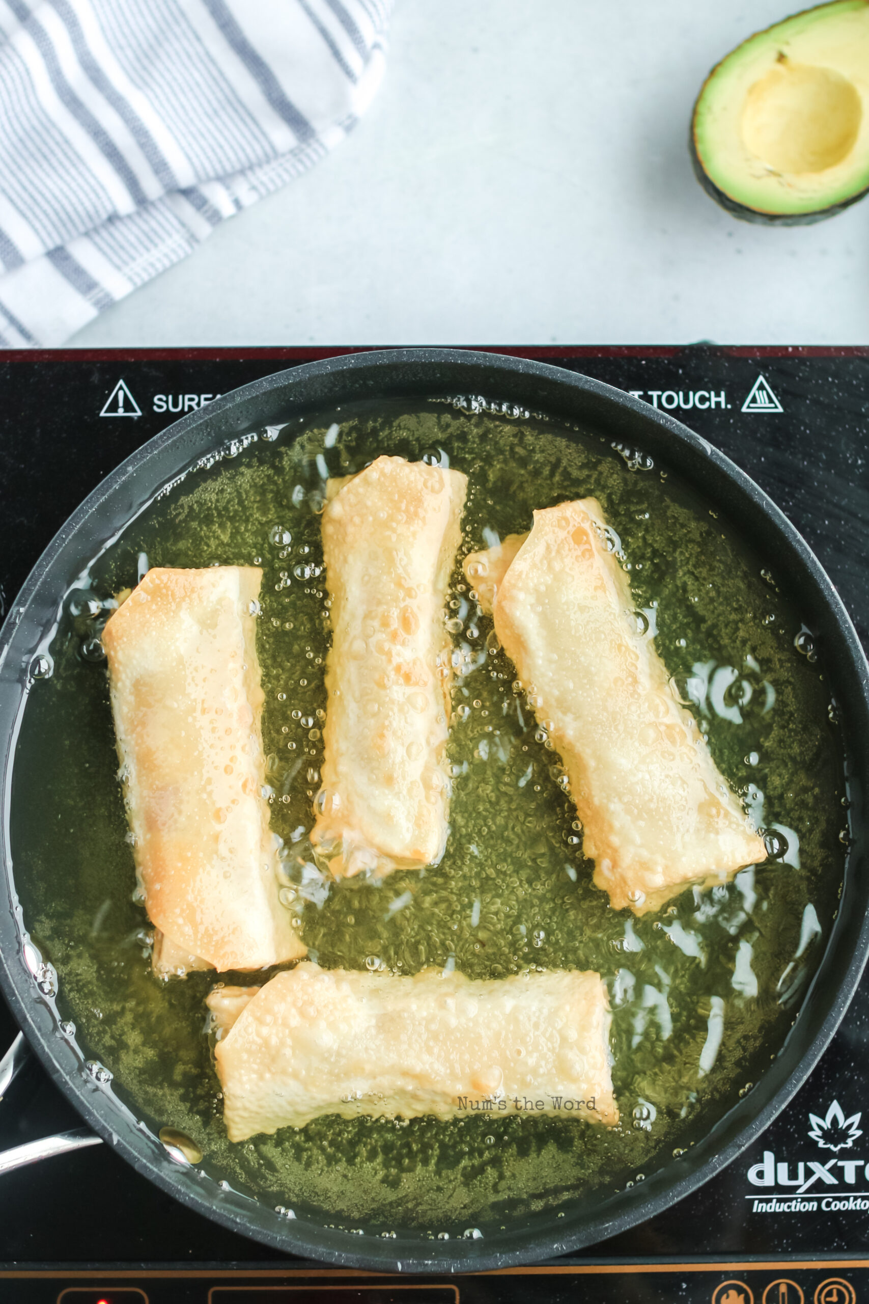 egg rolls being fried in oil in a skillet