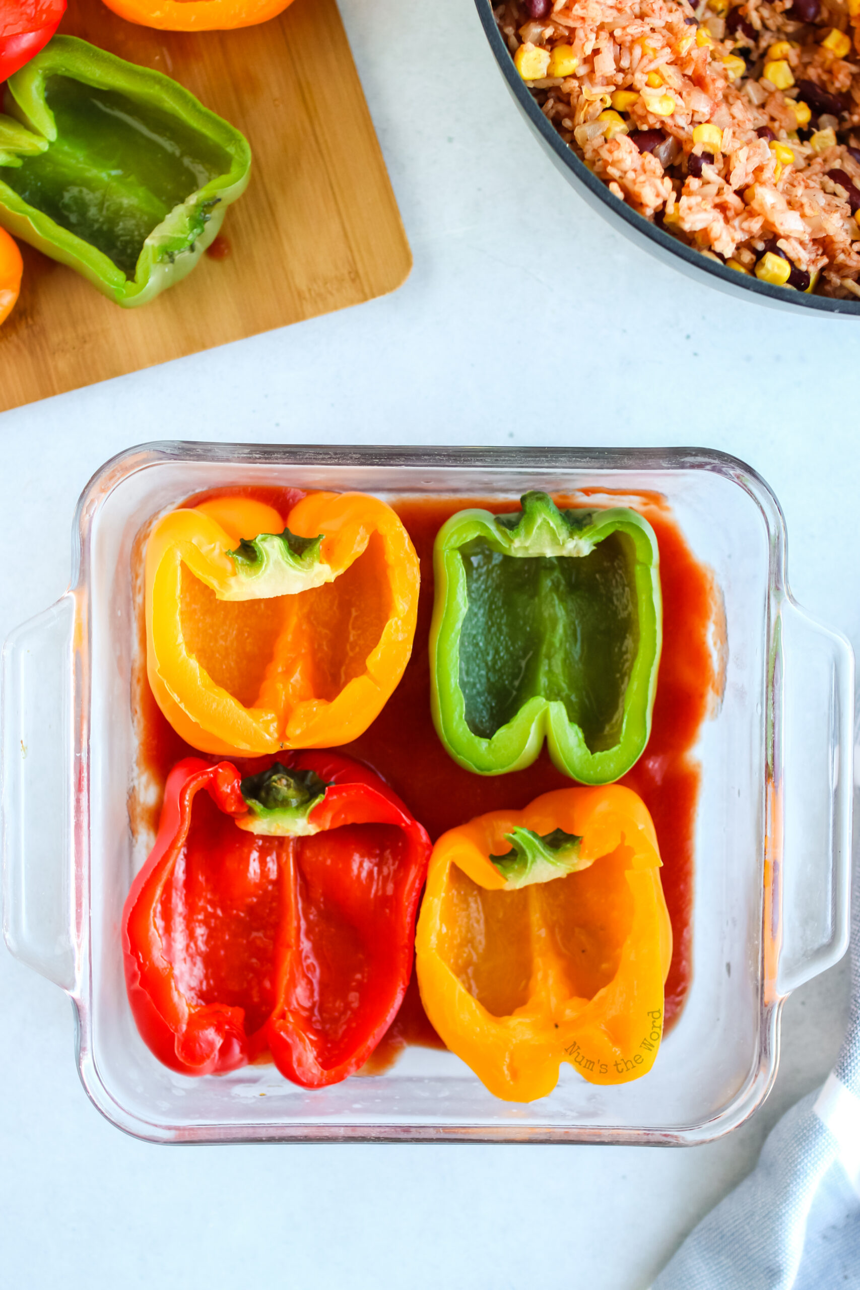 4 half bell peppers placed in a dish on top of tomato sauce.