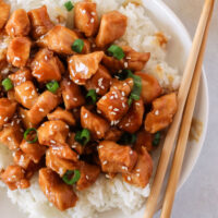 zoomed in image of chicken and rice with sesame seeds and green onions.
