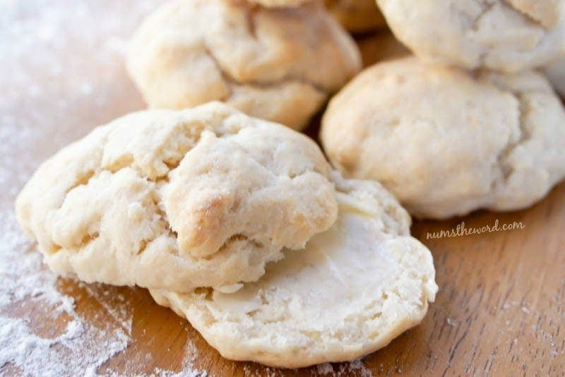 2 Ingredient Biscuits - Biscuits on a table with one cut in half and smothered in butter.