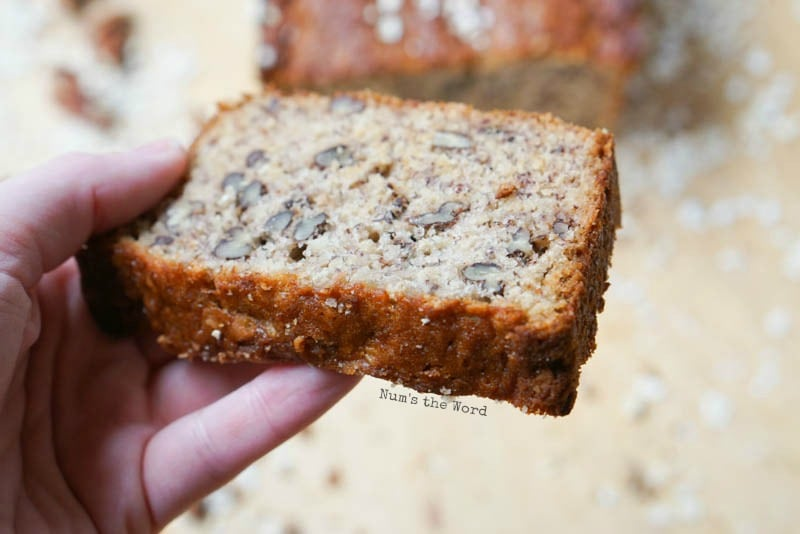 Oatmeal Pecan Banana Bread - hand holding a slice of bread to show details of what inside looks like.
