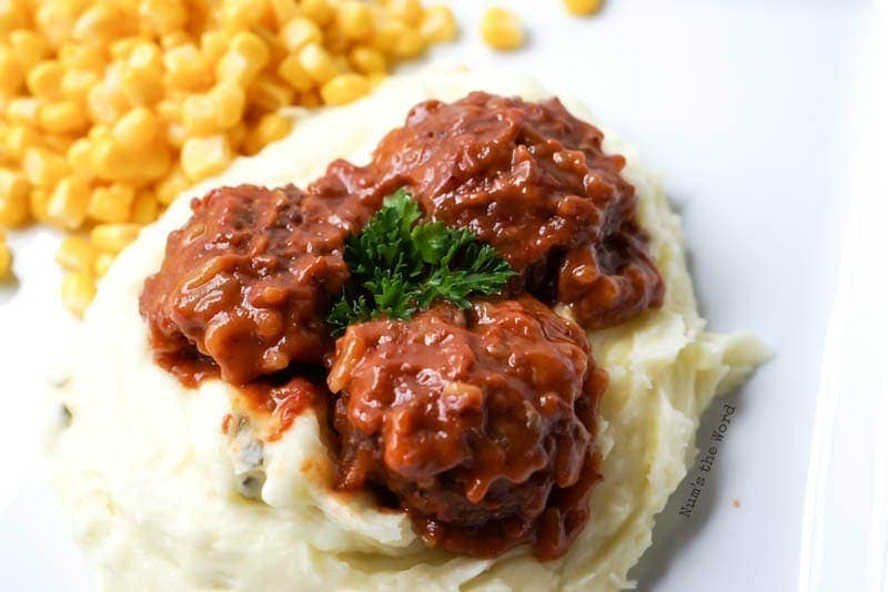 Porcupine Meatballs - Down side angle of plate with meatballs on mashed potatoes with corn on side
