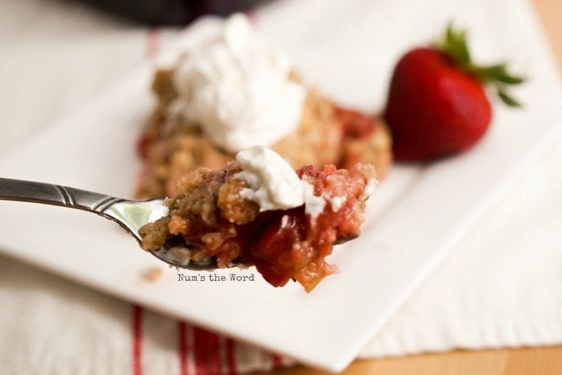 close up of strawberry rhubarb crisp on fork