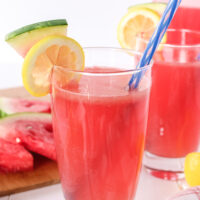 two glasses of watermelon lemonade with pitcher in background.