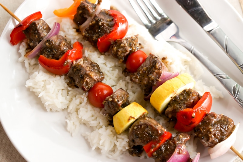 Marinated steak kabobs after grilling on a bed of rice
