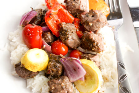 Close up photo of marinated steak kabobs over rice