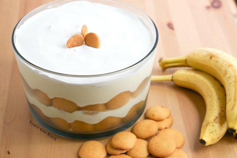 Thick & Creamy Banana Pudding - Angled shot of pudding in bowl with vanilla wafers and bananas next to bowl