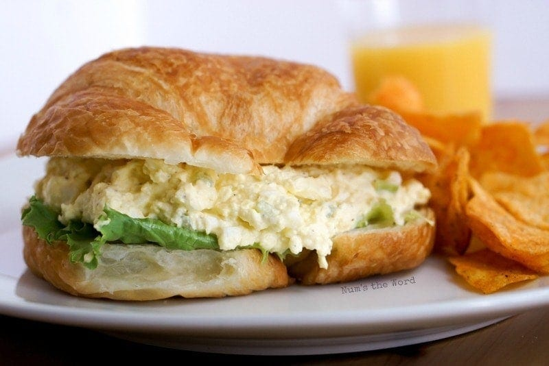 Deluxe Egg Salad - croissant on plate with chips and orange juice