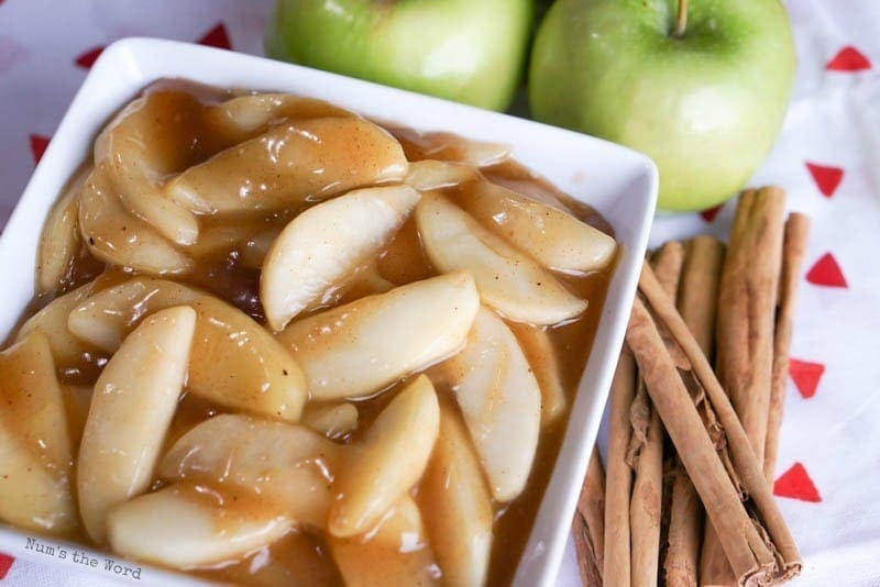 Sauteed Apples - close up of finished apples in bowl with fresh apples and cinnamon sticks next to bowl