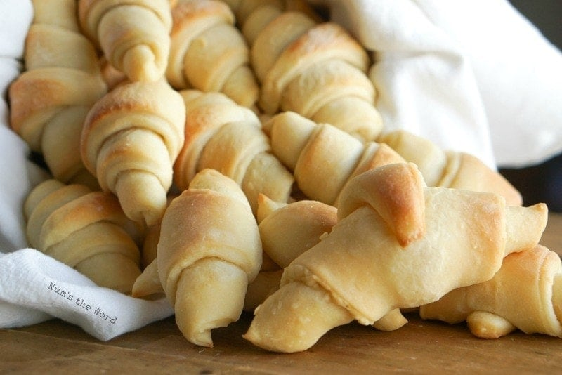 Simply Delicious Rolls - Fresh baked rolls in basket, spilling out on table