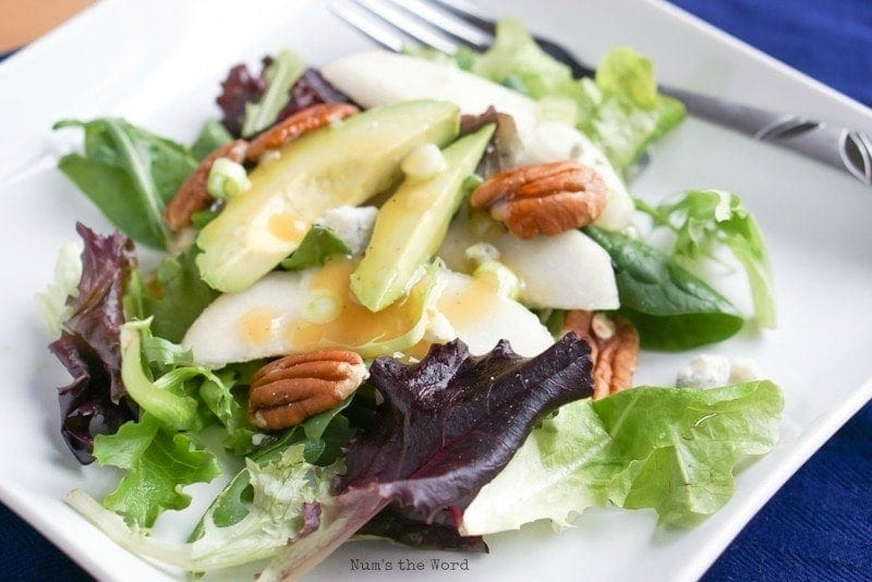 Roquefort Pear Salad - salad on plate with dressing on it
