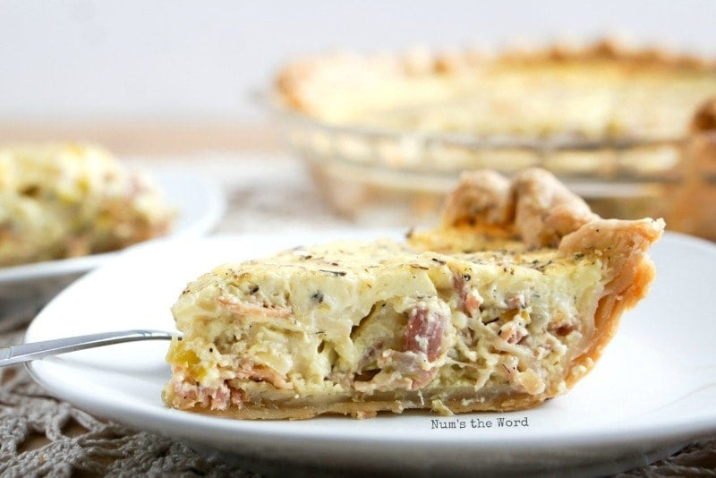 Quiche Lorraine - Cooked quiche sliced and on plate, side angle with rest of quiche in background