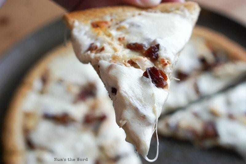 Chicken Bacon Ranch Pizza - a single slice being held up to camera to show off toppings and melted cheese