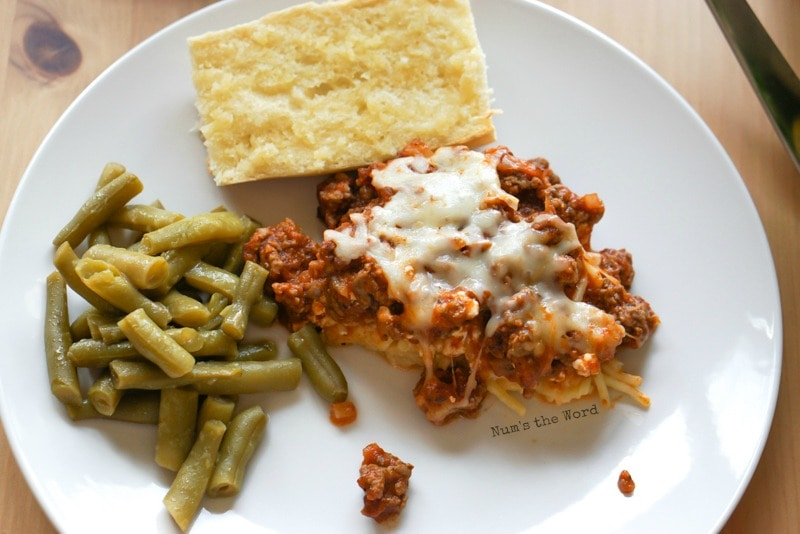 Spaghetti Casserole - casserole on plate with garlic bread and green beans. Photo taken from above.