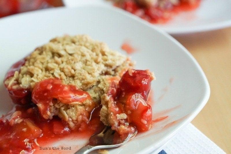Cherry Rhubarb Crisp - two plates of crisp and pan of crisp in background. Fork full of crisp ready to be eaten.