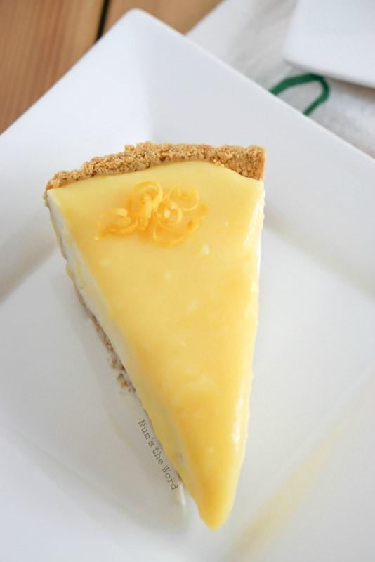 No Bake Lemon Cheesecake - single slice of cheesecake on a plate with a little lemon zest on top. Photo view from the top looking down.