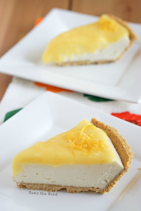 No Bake Lemon Cheesecake - single slice of cheesecake on a plate with a little lemon zest on top. Photo view from the side with a second slice in the background