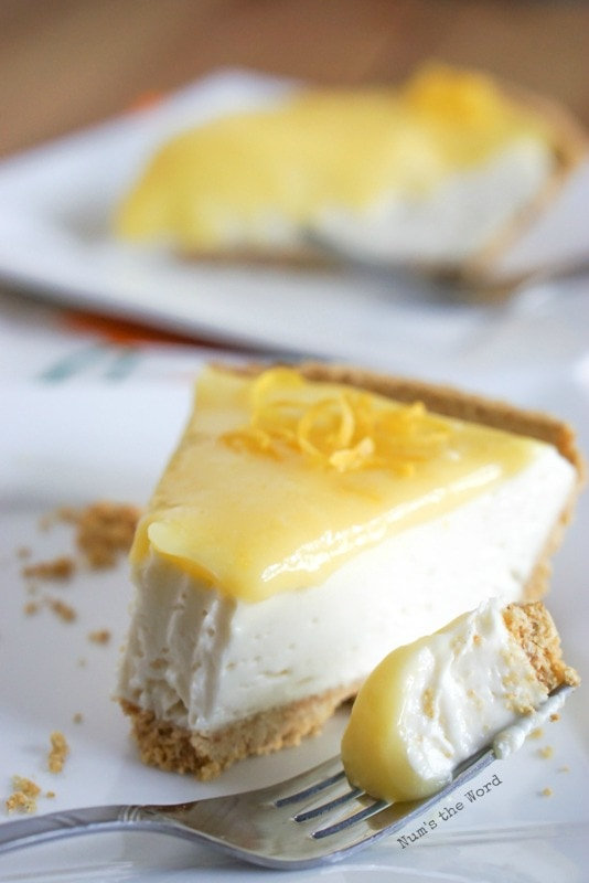 No Bake Lemon Cheesecake - two slices of cheesecake. One has a a fork full of the cheesecake next to it ready to be eaten.