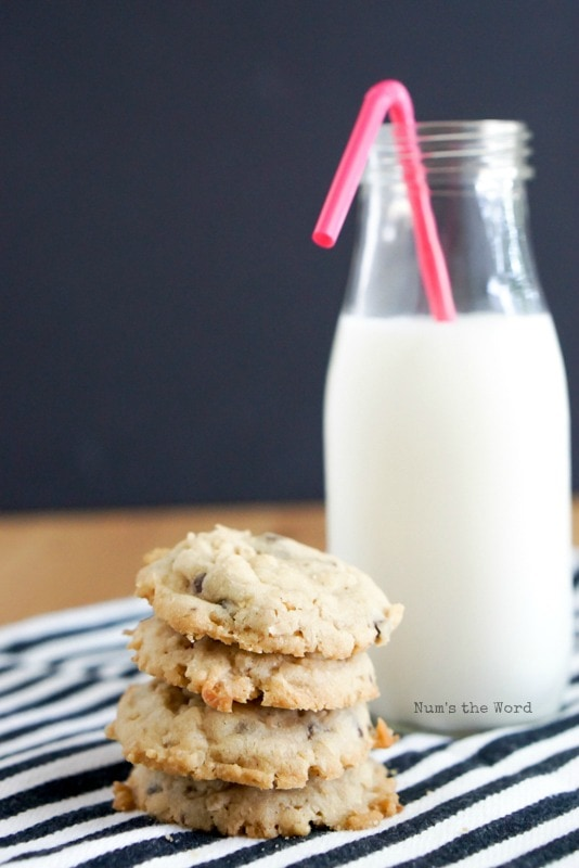 Krispy Coconut Oatmeal Cookies - 3 cookies stacked with glass of milk behind.