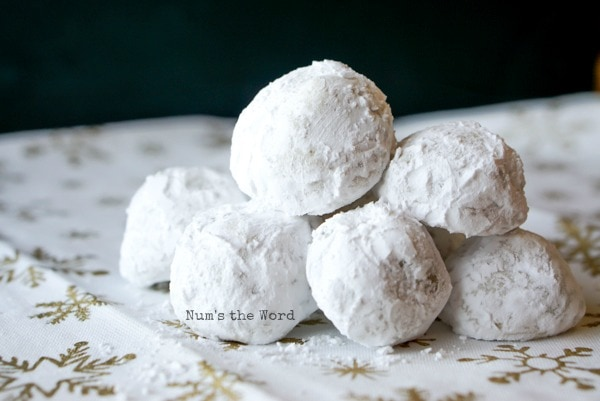 Surprise Snowball Cookies - cookies sitting on a snowflake cloth stacked up on each other.