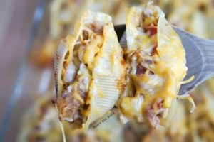 Pulled Pork Stuffed Shells - two stuffed shells, cooked and on a wooden spoon about to be placed on a plate.