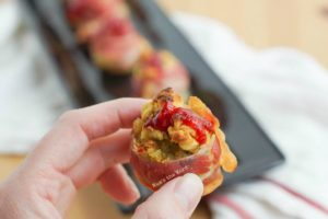 Bacon Wrapped Stuffing Bombs - hand holding a bacon bomb with a dollop of raspberry sauce.