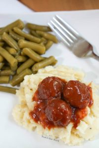 Chili Cranberry Meatballs - meatballs over mashed potatoes on plate with green beans