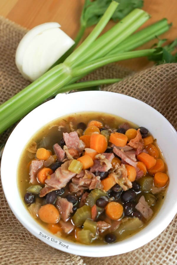 Ham Bone & Vegetable Soup - zoomed out image soup with onion and celery next to