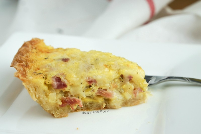 Ham & Cheese Quiche - slice of quiche on a plate, side view.