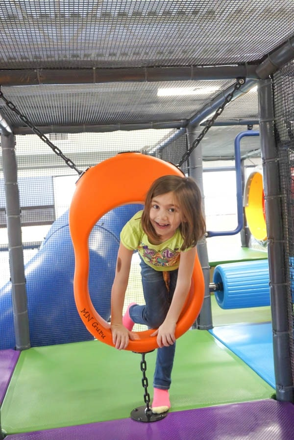 Sartell Community Center - girl climbing through obstacle item