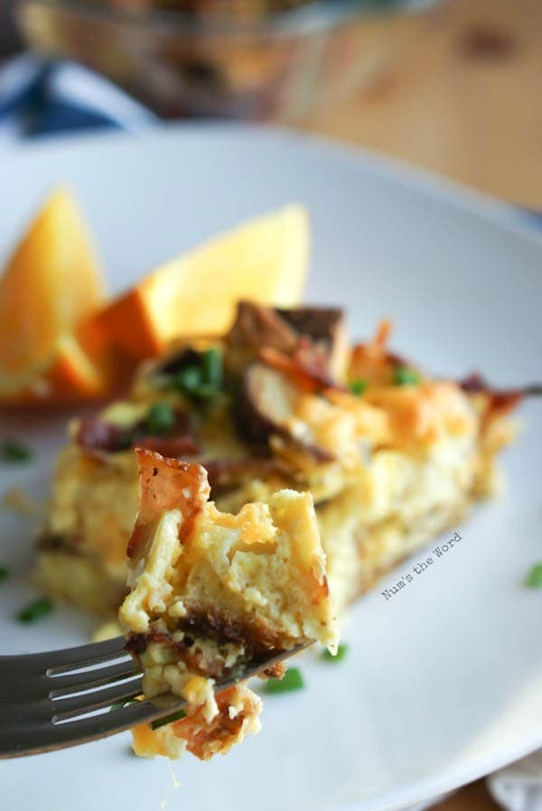 Bacon, Egg & Cheese Strata - fork full of strata with slice of strata in background.