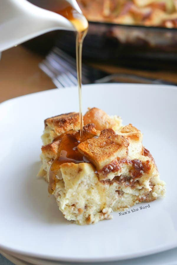 Bagel French Toast Casserole - slice of casserole on plate with maple syrup being drizzled over.