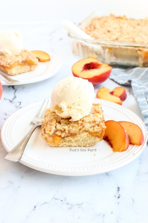 Fresh Peach Crumb Bars - baked bar on a plate with a scoop of vanilla ice cream.