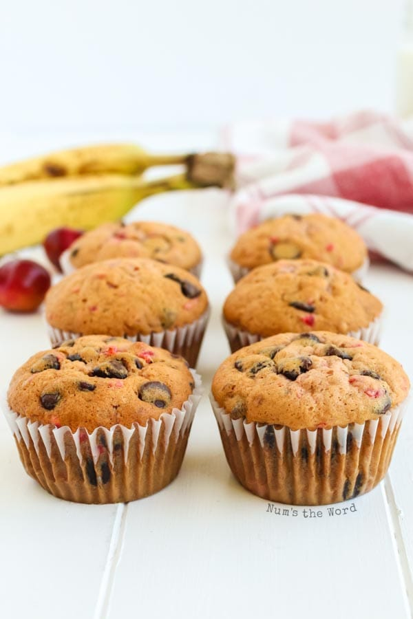 Banana Chocolate Chip Muffins - 6 muffins on counter with bananas and cherries in background