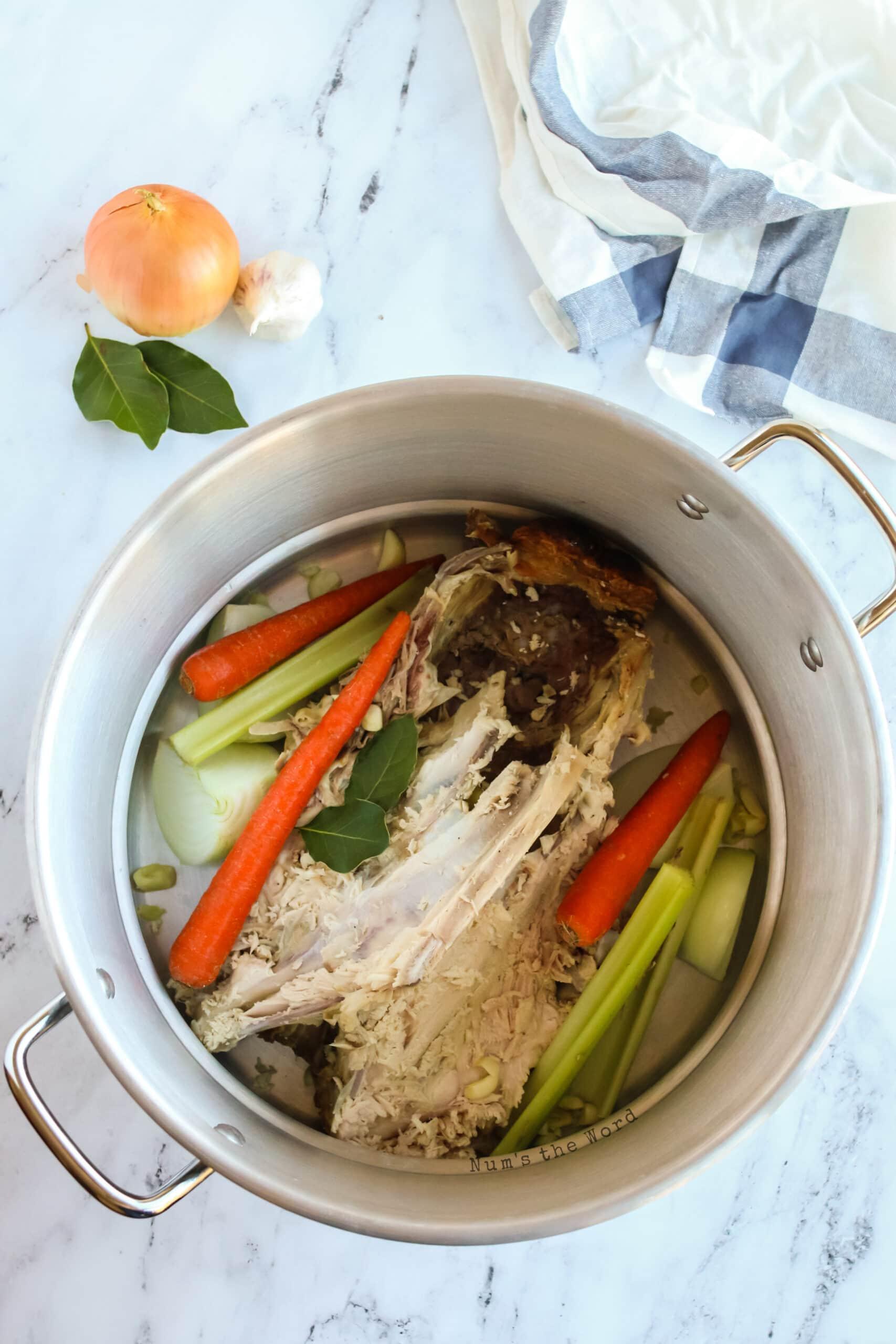 vegetables added to turkey bones in large pot