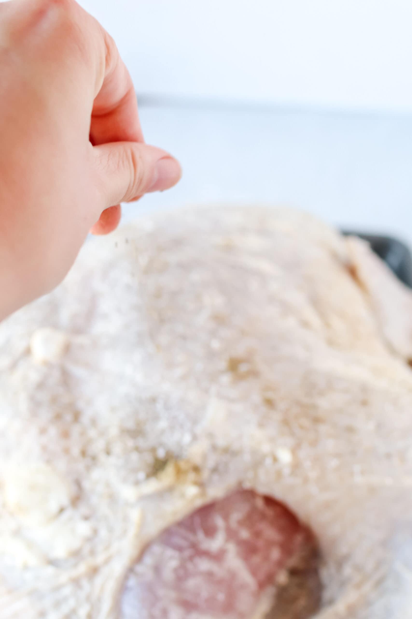 hand adding salt to turkey