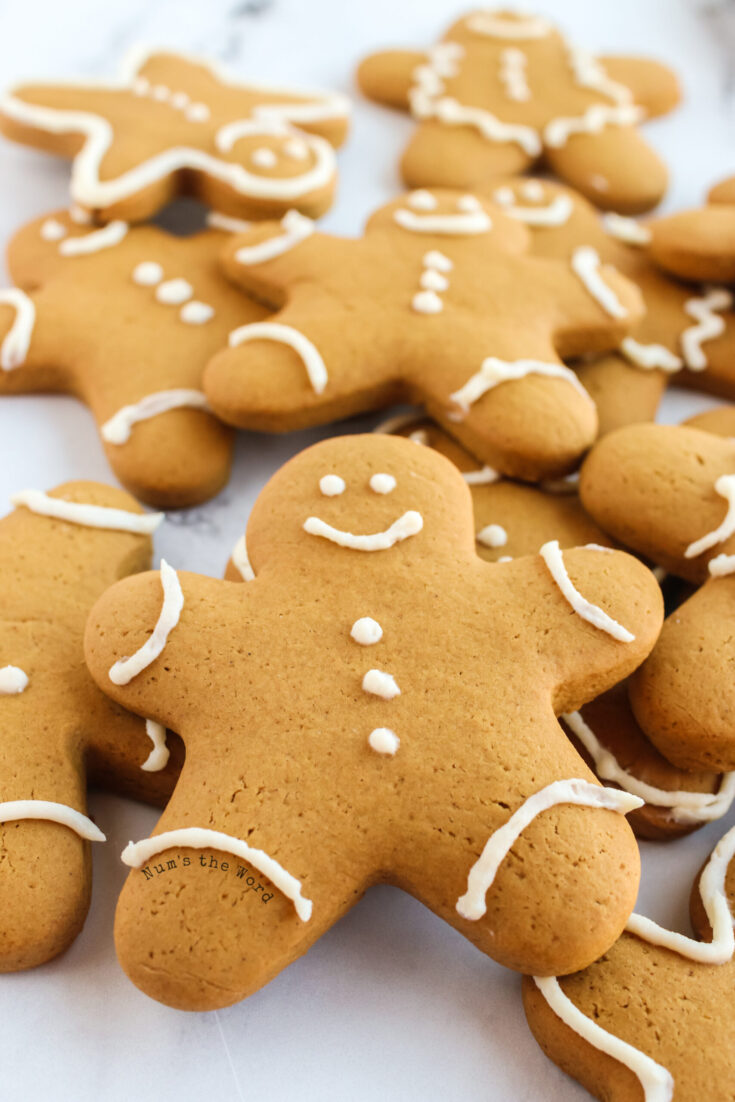 zoomed in image of decorated gingerbread cookies on parchment paper stacked on top of each other