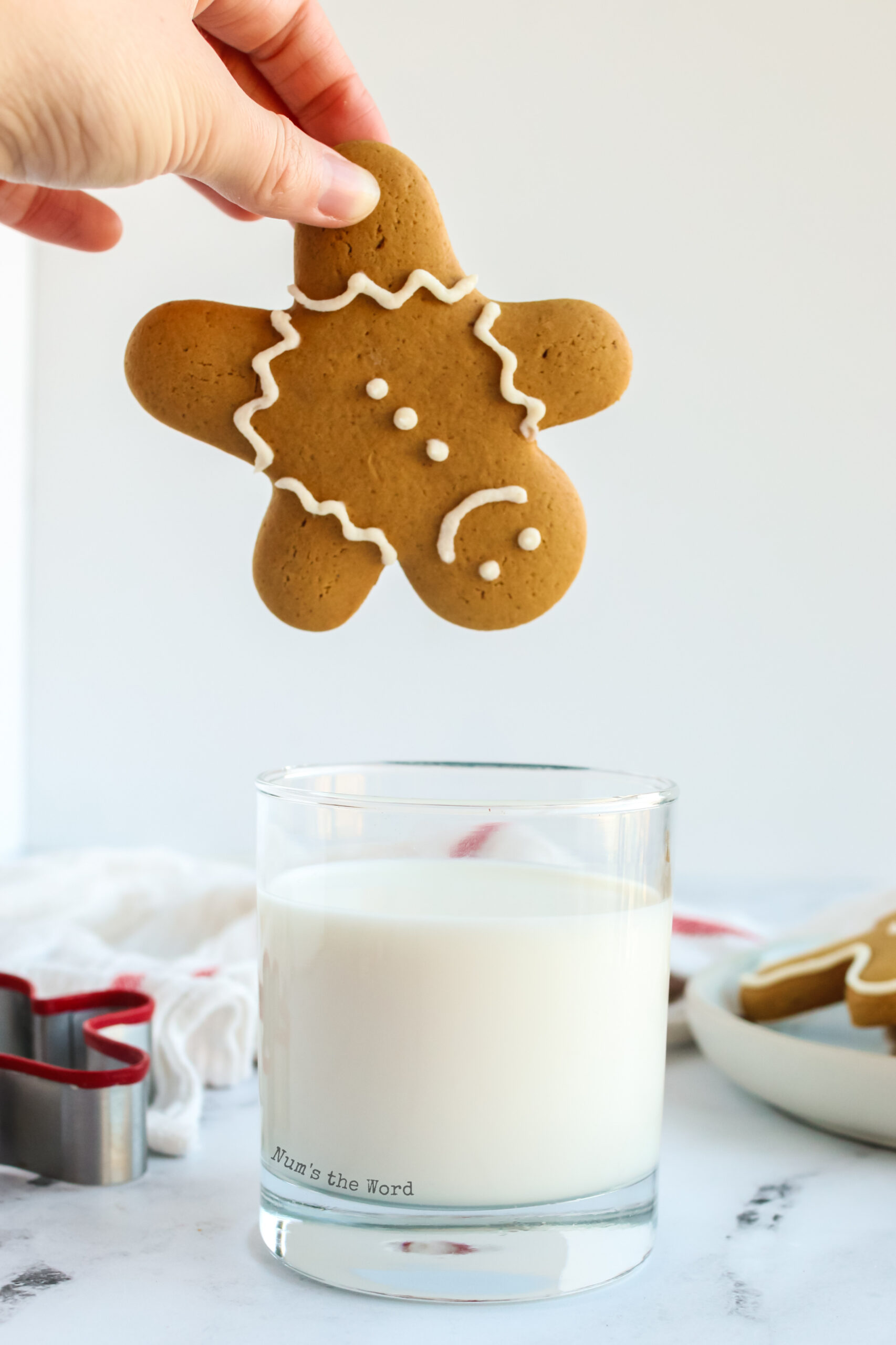 decorated gingerbread cookie being held upside down and ready to be dunked into a glass of milk