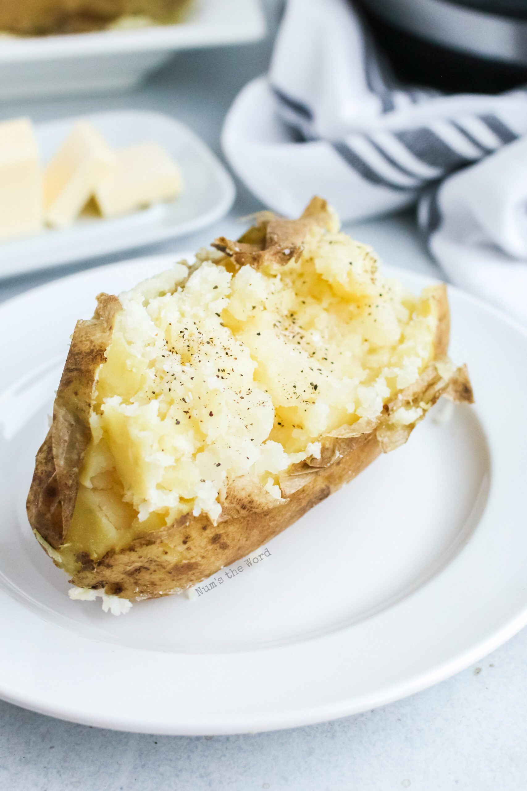Single baked potato on a plate with salt and pepper