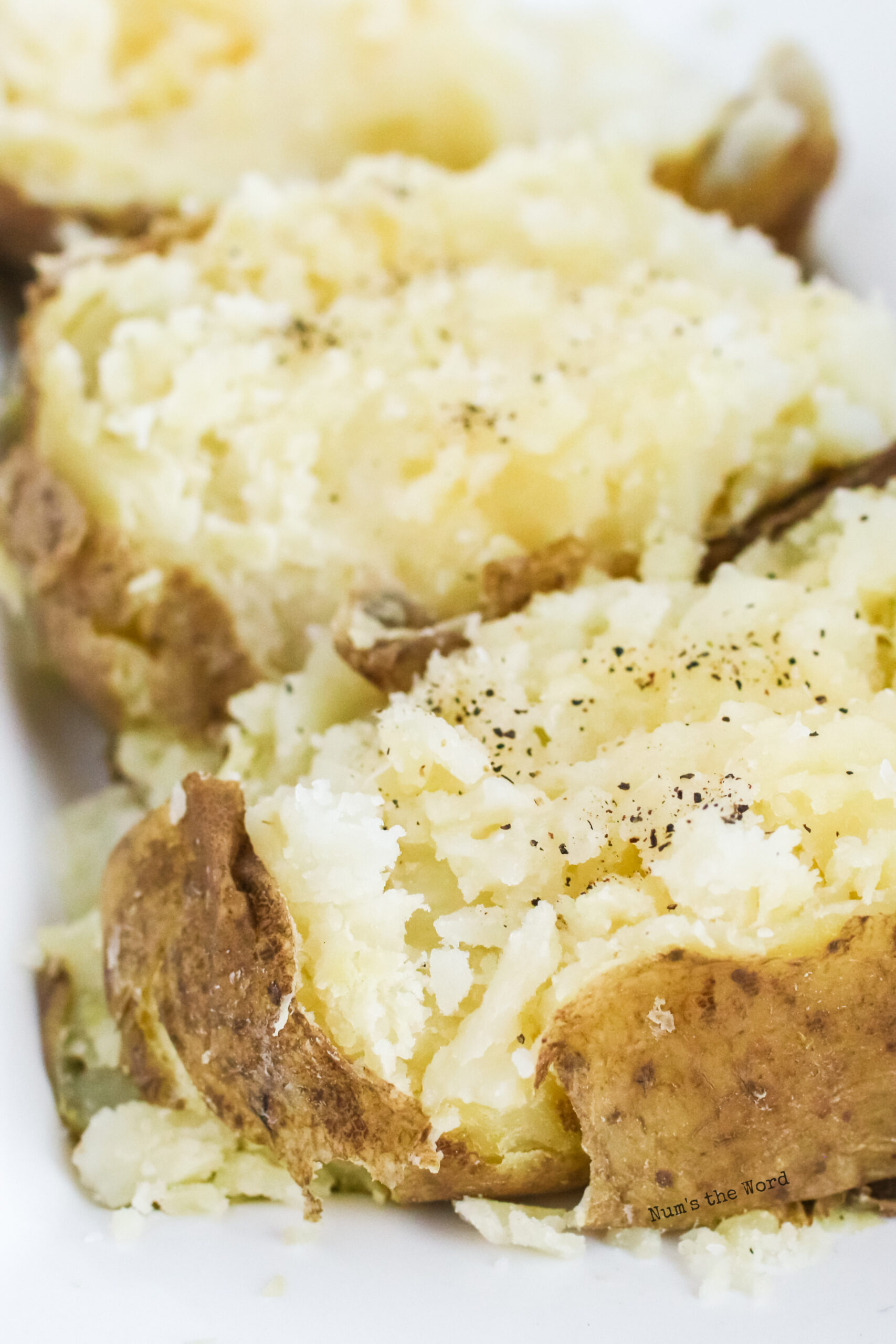 close up of two baked potatoes on platter. Closest one has salt and pepper on it.