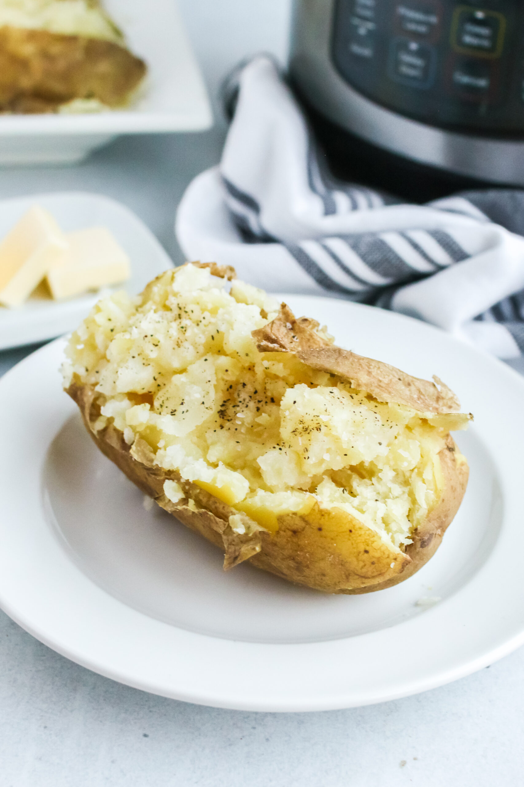 a single baked potato on a plate with instant pot in background