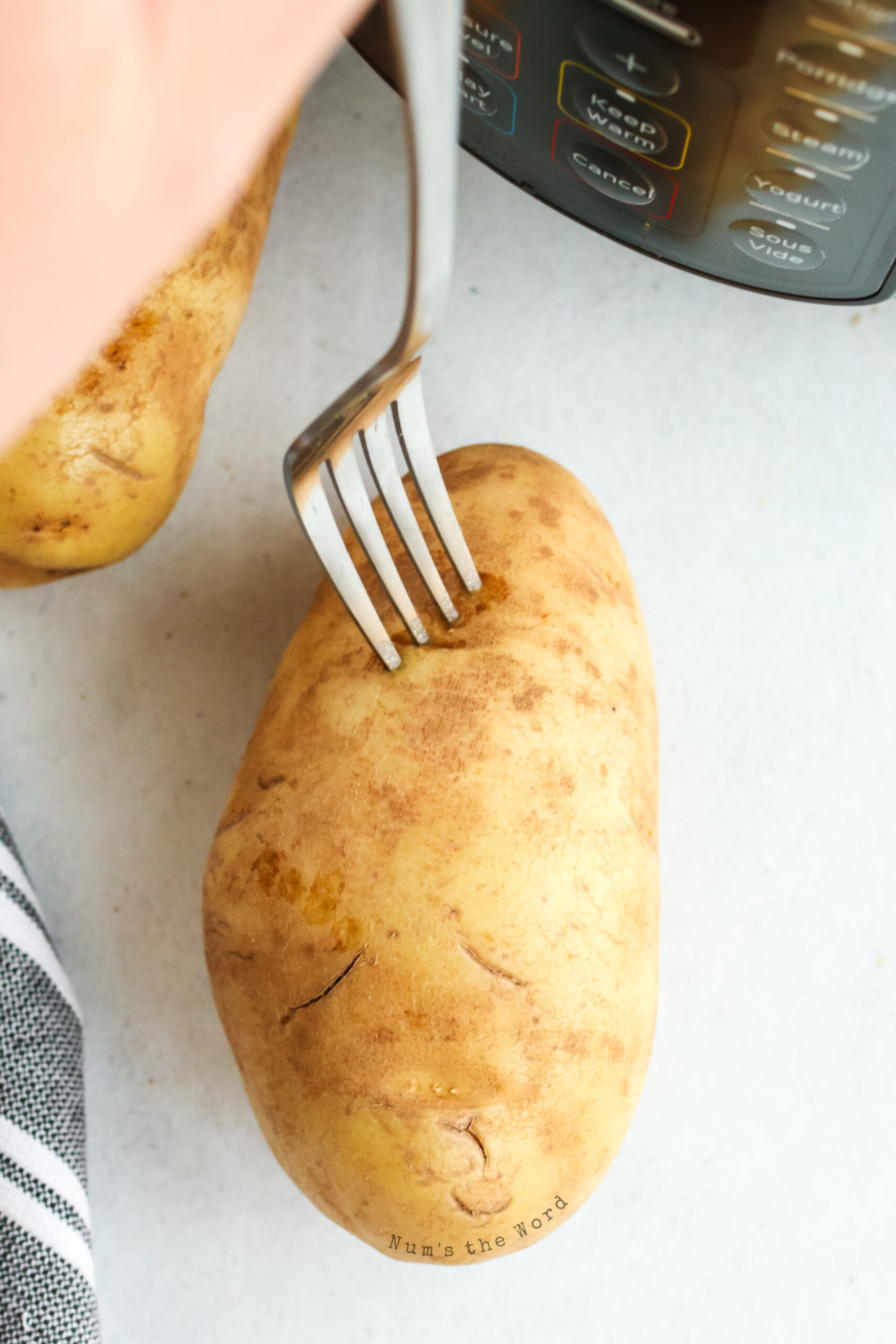 fork pricking a washed and uncooked potato