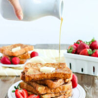 4 pieces of french toast stacked on a plate with a pat of butter and syrup being poured over the top.